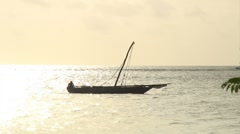 Stock Video Footage of African fishing boat with mast sets out at sunrise on Zanzibar