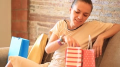 Attractive cheerful woman with shopping bags sitting on sofa HD Stock Footage