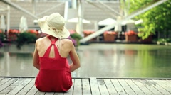Young beautiful woman sitting by the water in urban environment HD Stock Footage