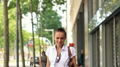 Woman with shopping bags walking in the city, steadicam shot Stock Footage