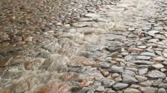 Stream of rain on the cobble road - stock footage