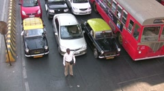 Police man watches Mumbai traffic go by (overhead), India Stock Footage