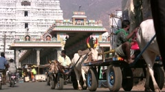 Cow carts and other traffic in front of a Hindu temple Stock Footage