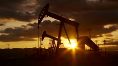 Oil well piston pumps at sunset Stock Footage