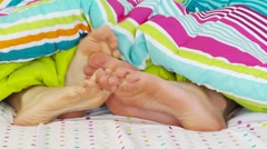 Couple playing with feet under covers in bed Stock Footage