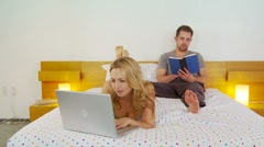Young couple reading and using laptop Stock Footage