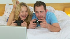 Young couple playing video games in bed Stock Footage