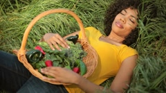 Young woman lying in field with basket of vegetables Stock Footage