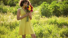 Young woman holding flowers in field Stock Footage