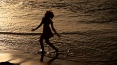 Silhouette of young woman dancing on beach - stock footage