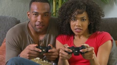 Couple playing video games on couch Stock Footage