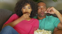 Couple watching movie on couch while eating popcorn Stock Footage