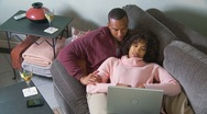 Couple with computer on couch Stock Footage