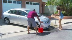 Couple washing car in driveway - stock footage