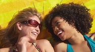 Stock Video Footage of Two women friends lying in the sun laughing