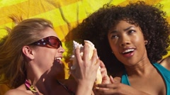 Two women friends playing with seashell Stock Footage