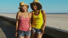 Two women friends at the beach in cowboy hats - stock footage