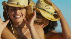 Two women friends at the beach in cowboy hats Stock Footage