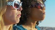 Stock Video Footage of Two women friends in sunglasses blowing bubblegum at the beach
