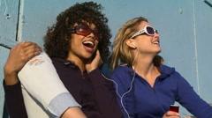 Two women friends listening to music at the beach Stock Footage