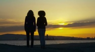 Stock Video Footage of Two women friends raising their arms on the beach at sunset