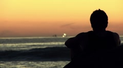Silhouette of Young Man Staring at Ocean, Rack Focus Stock Footage