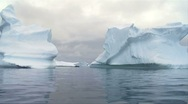 Stock Video Footage of two icebergs with small boat in between