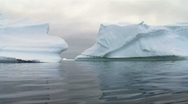 Stock Video Footage of two huge icebergs in antarctica, reflected in the ocean