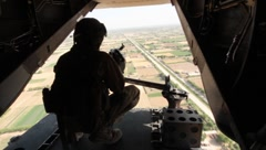 Marine with machine gun looking out of a helicopter onto fields(HD)k - stock footage