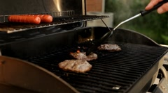 Burgers cooking on grill in hot sun Stock Footage