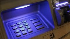 Placing card into ATM and putting in pin - stock footage