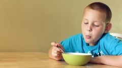 Young Boy eating a bowl of cereal - stock footage