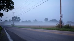 Cars driving by on foggy back road Stock Footage