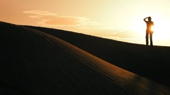 Distant Figure Watching the Sun on Sand Dunes - stock footage