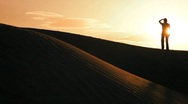 Stock Video Footage of Distant Figure Watching the Sun on Sand Dunes