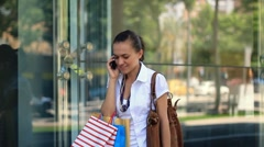 Woman with shopping bags walking and talking on mobile phone, slow motion Stock Footage