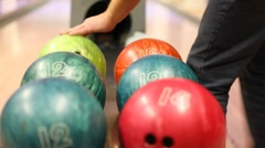 Stock Video Footage of Close-up of bowling balls, man takes ball