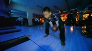 Boy wearing spectacles throws ball in bowling club Stock Footage