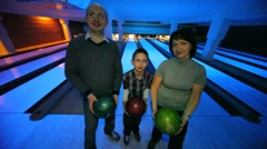Family stay with balls and show them in bowling club Stock Footage