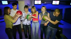Six friends stay and laugh with balls in bowling club Stock Footage