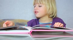 Little girl read a picture-book Stock Footage