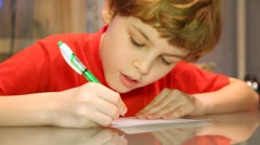 Stock Video Footage of boy writes something very attentively
