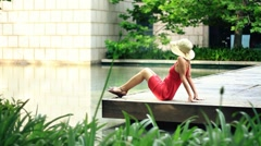 Happy beautiful woman relaxing by the water in urban environment Stock Footage
