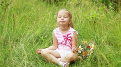 Llittle girl in lotus position. She plays the fool. Stock Footage