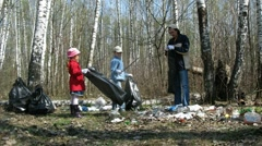 Children and their father collect trash to garbage bags in forest Stock Footage