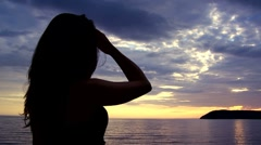 Young woman watching the sunset and touching hair slowmotion Stock Footage