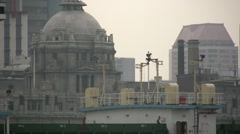 Closeup of cargo vessel sailing past the Bund in Shanghai China Stock Footage