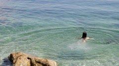 Woman jumping from the sea. Reverse video Stock Footage