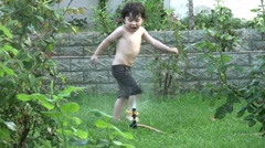 Little boy plays in the water at a garden Stock Footage