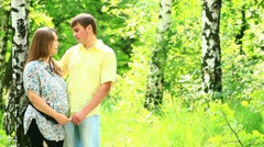 Happy pregnant couple talking in a holiday park Stock Footage